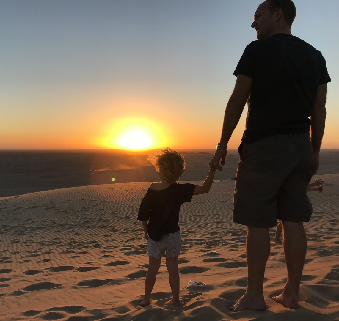 11 incredible things to do in Qatar - Mr Wanderlust and Thing 2 watching the sun set at the singing sand dunes