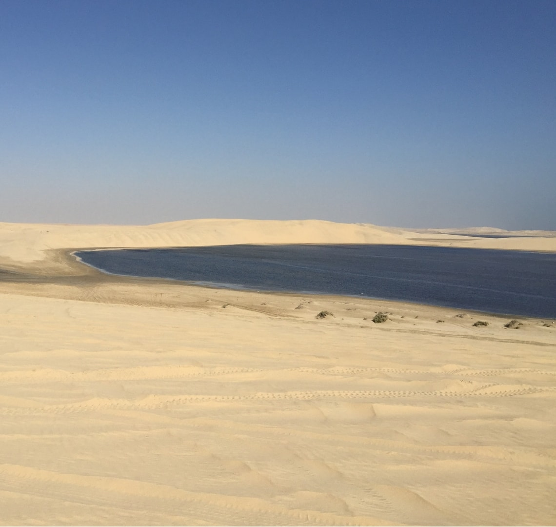 11 incredible things to do in Qatar - sea next to sand dunes