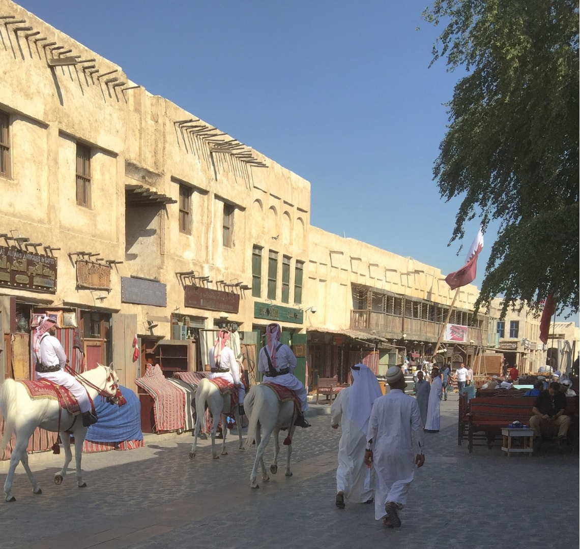 11 incredible things to do in Qatar - men on horseback riding through the outside part of the souq