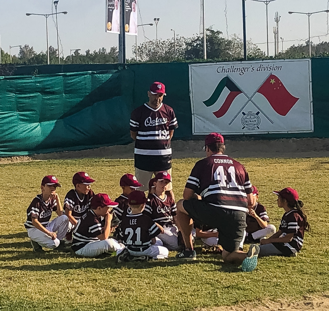 Baseball Mom - Thing 1 with his teammates. They are all sat on the grass listening to their coach.