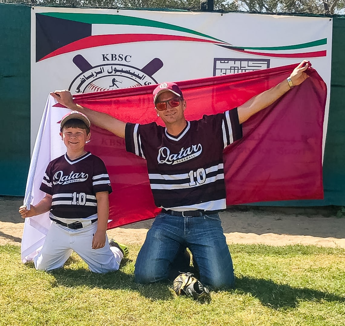 Baseball Mom - Thing 1 and Mr Wanderlust kneeling on the grass with the Qatar flag