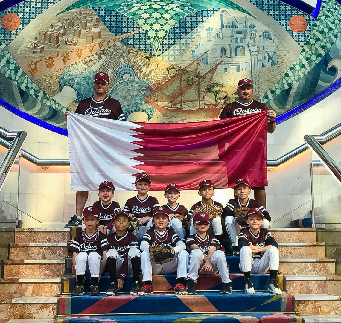 Baseball Mom - Thing 2 with 2 of his coaches and his 9 teammates sitting on the stairs in the hotel. The coaches are standing behind them holding the Qatari flag.