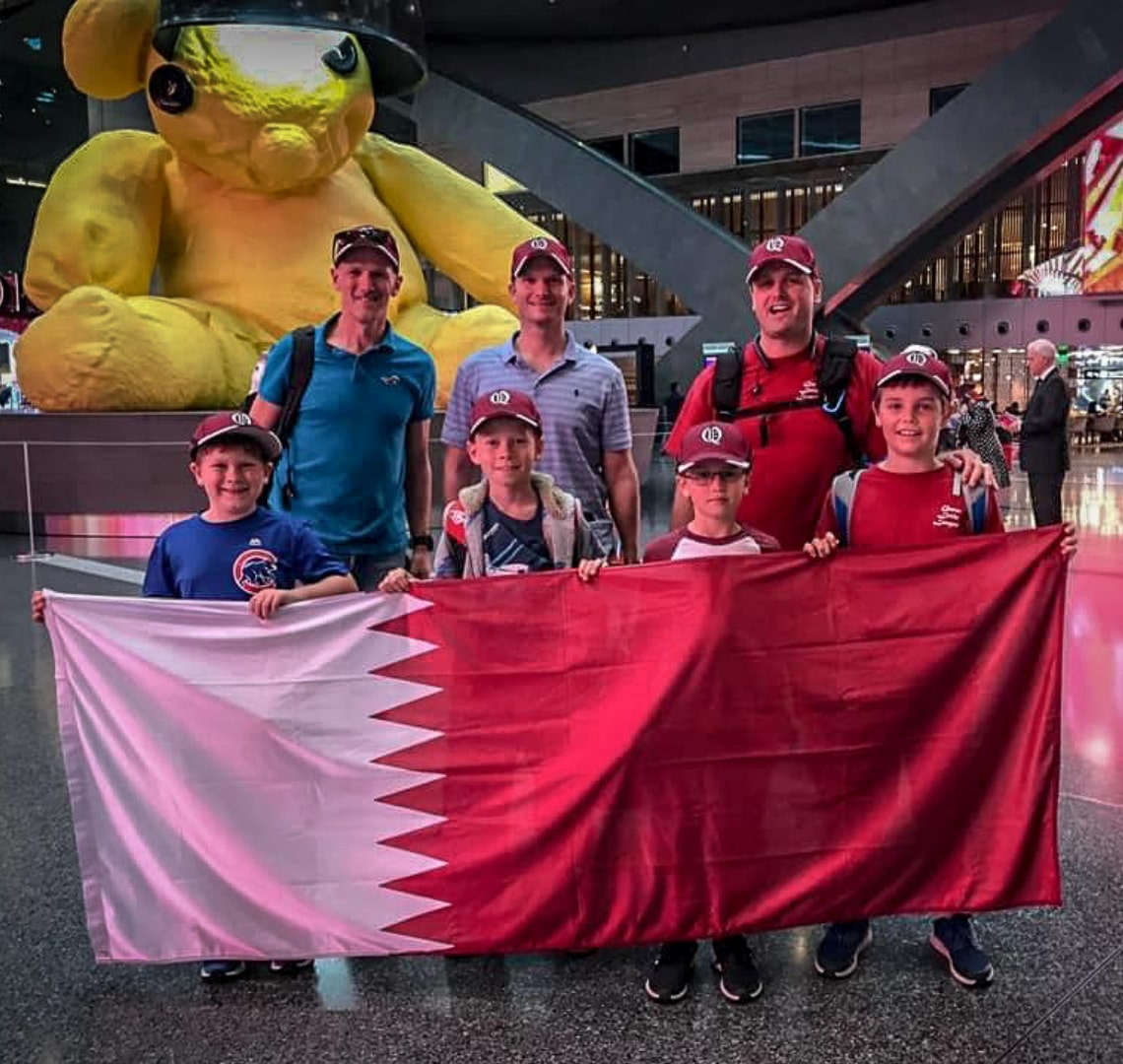 Baseball Mom - Thing 1 (far left) with 3 of his teammates clutching the Qatar flag. 3 dads are stood behind them and they're all stood in front of the iconic yellow teddy bear in Hamad International Airport