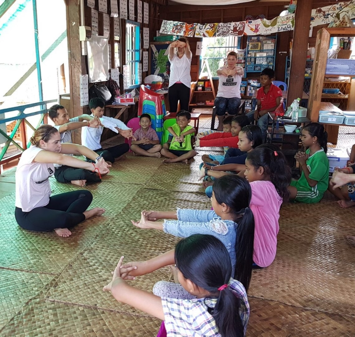 Volunteer tourism - a yoga class with some of the volunteers and the kids at Treak. Everyone is sat on the floor with their arms stretched out in front of them and their hands clasped