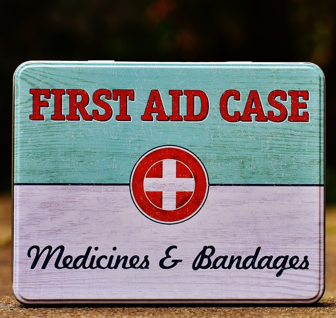 "Safari first aid Kir - a stock photo of an old / retro fist aid box in white and turquoise with red writing. It says ""FIRST AID CASE - Medicines & Bandages""."