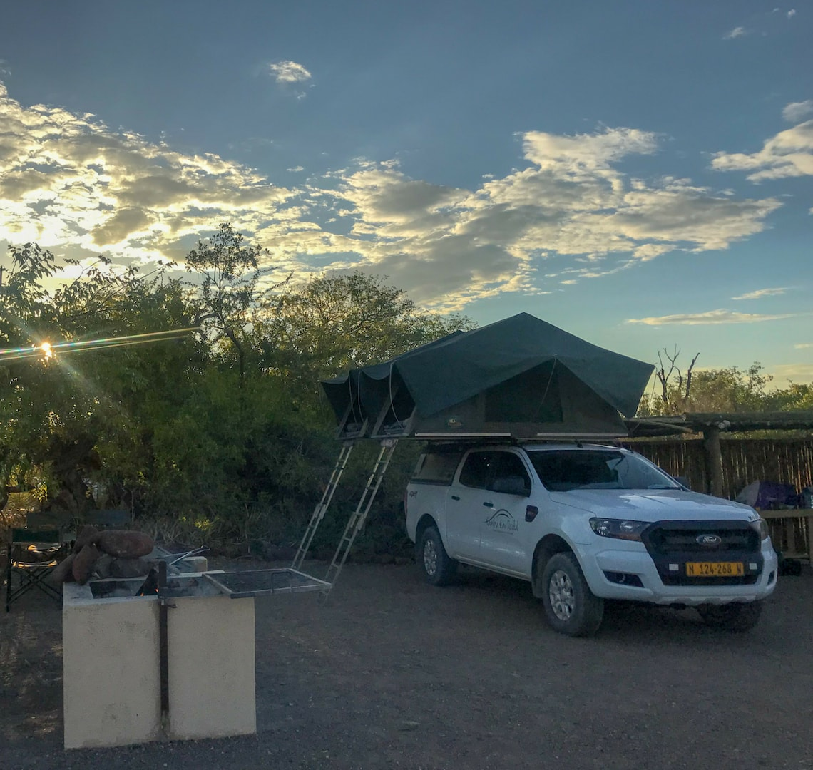 "Self Drive Safari Namibia - the car at one of our campsites all set up with the 2 tents ""popped up"" on top. The sun is setting in the background."