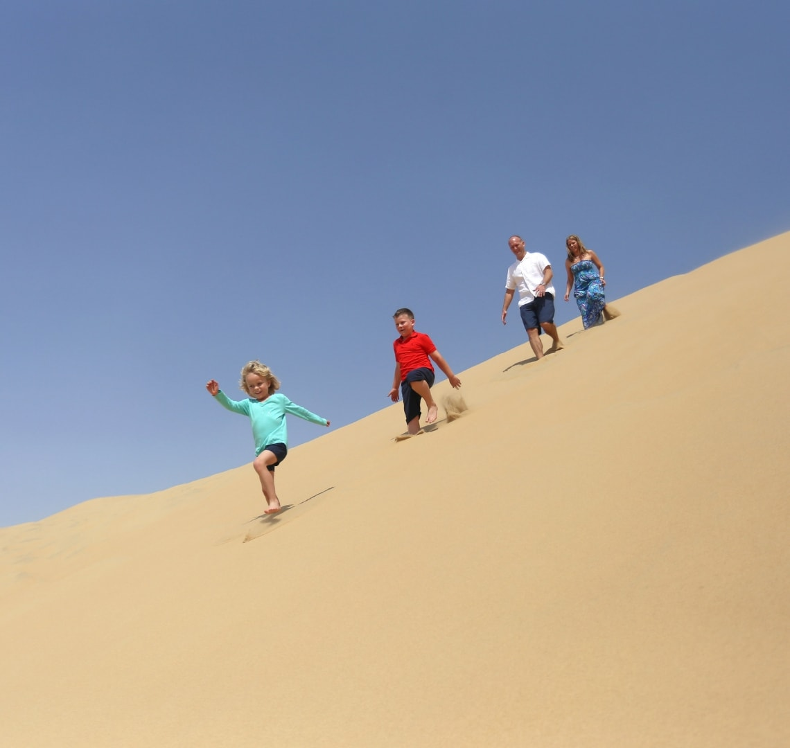 When the end is in sight -our family walking down a sand dune