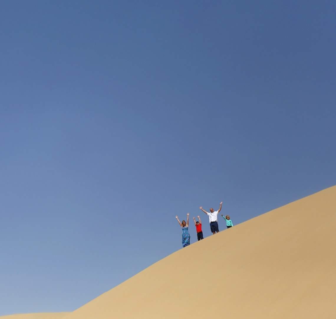 When the end is in sight - - our family stood at the top of a sand dune with our arms in the air