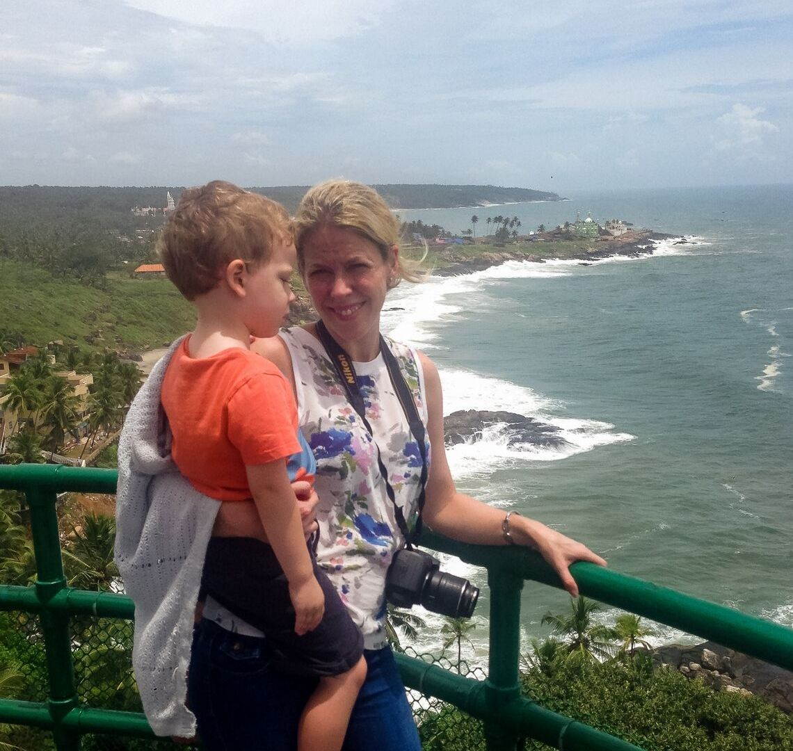 10 Day Kerala Itinerary - me carrying Thing 1 on my hip looking at the view from Kovalam Lighthouse 10 day Kerala Itinerary!