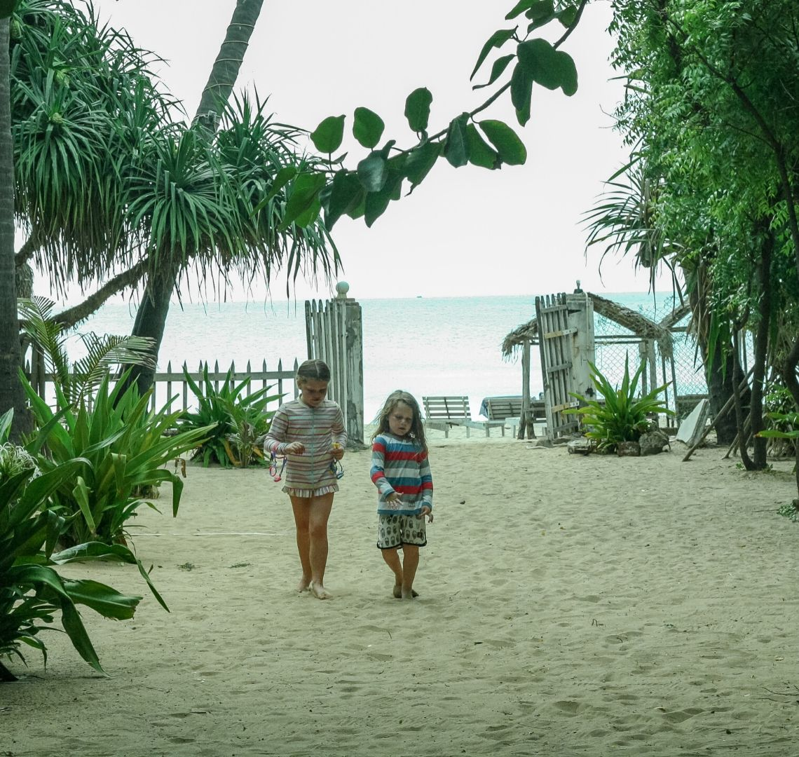 2 sisters walking up a sandy path among palm trees on Uppuveli Beach