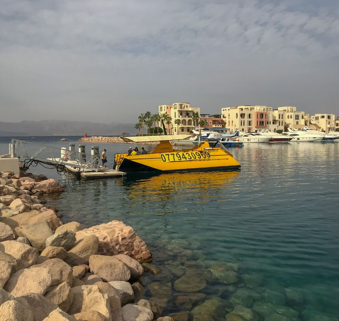 Things To Do In Jordan - Aqaba Red Sea Submarine - a yellow submarine floats in the clear blue waters of the marina waiting to pick up it's next customers and show them the depths of the Red Sea