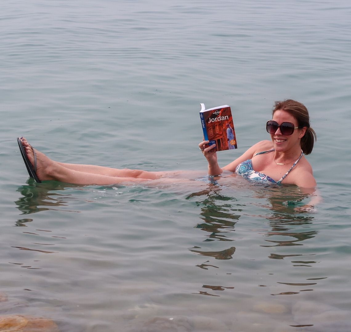 Things To Do In Jordan - Dead Sea - I am floating sitting up and pretending to read the Lonely Planet - Jordan
