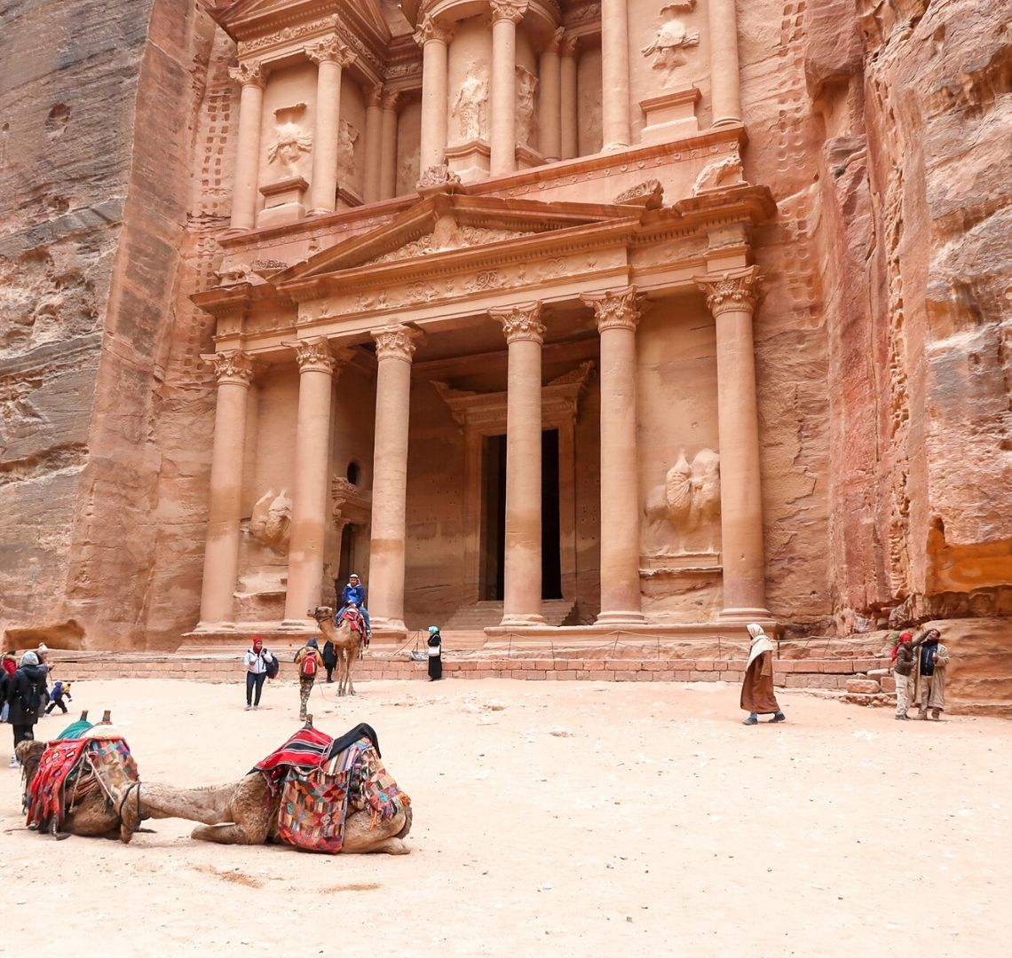 Things To Do In Jordan - Petra's Treasury stands majestically in the background with some tourists taking pictures of it. Two camels are lying down in the sand in the foreground.