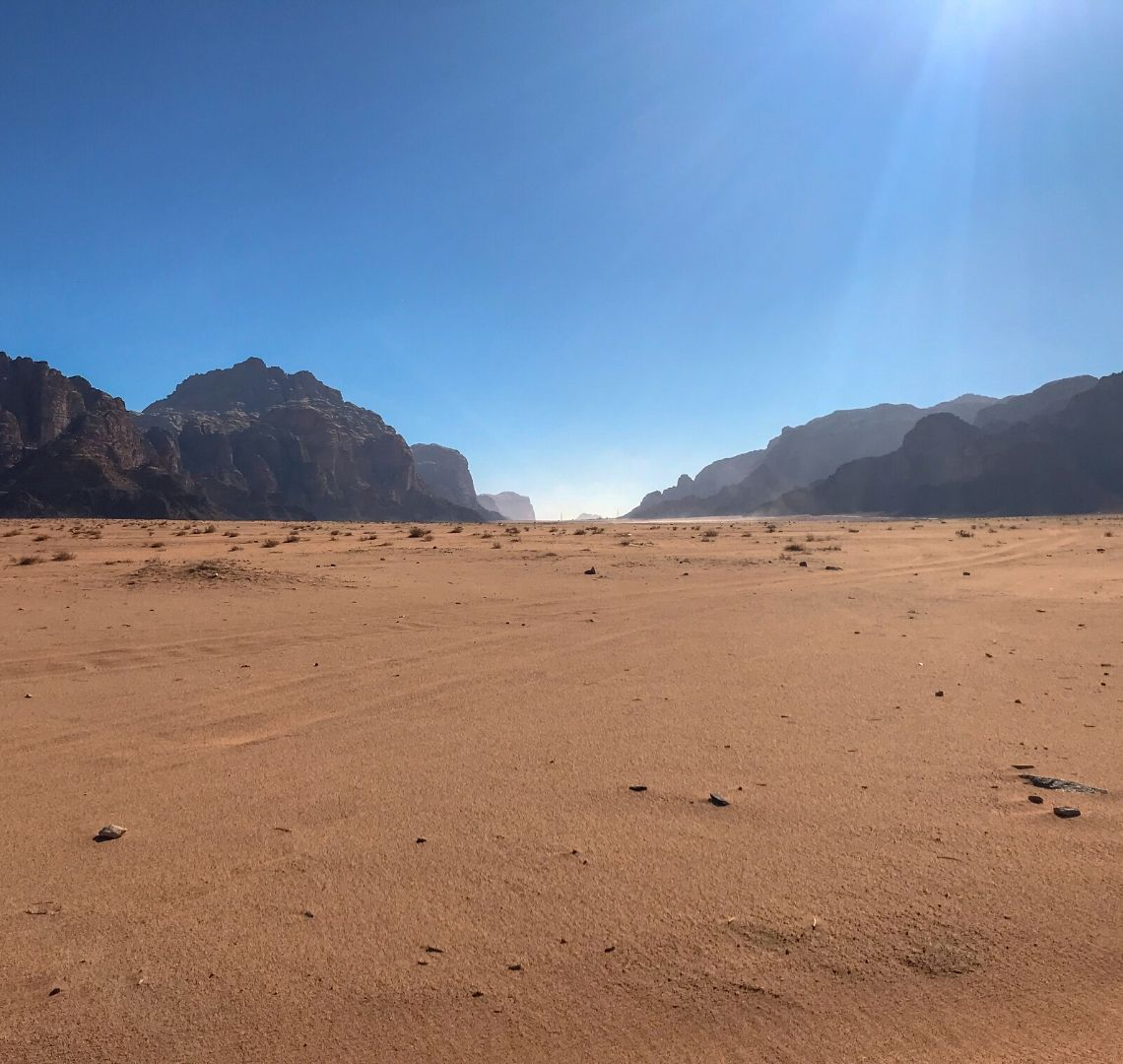 Things To Do In Jordan - Wadi Rum - a sun flare to the top right in a clear blue sky. Craggy rocks can be seen in the distance and between them some haze. In the foreground is an expanse of orange sand.