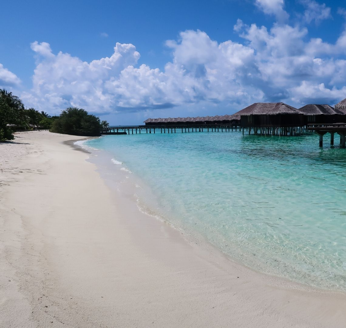 Maldives Activities Beach - a white sandy beach is on the left of the image, clear turquoise shallow water is in-between the beach and the water bungalows on stilts on teh right