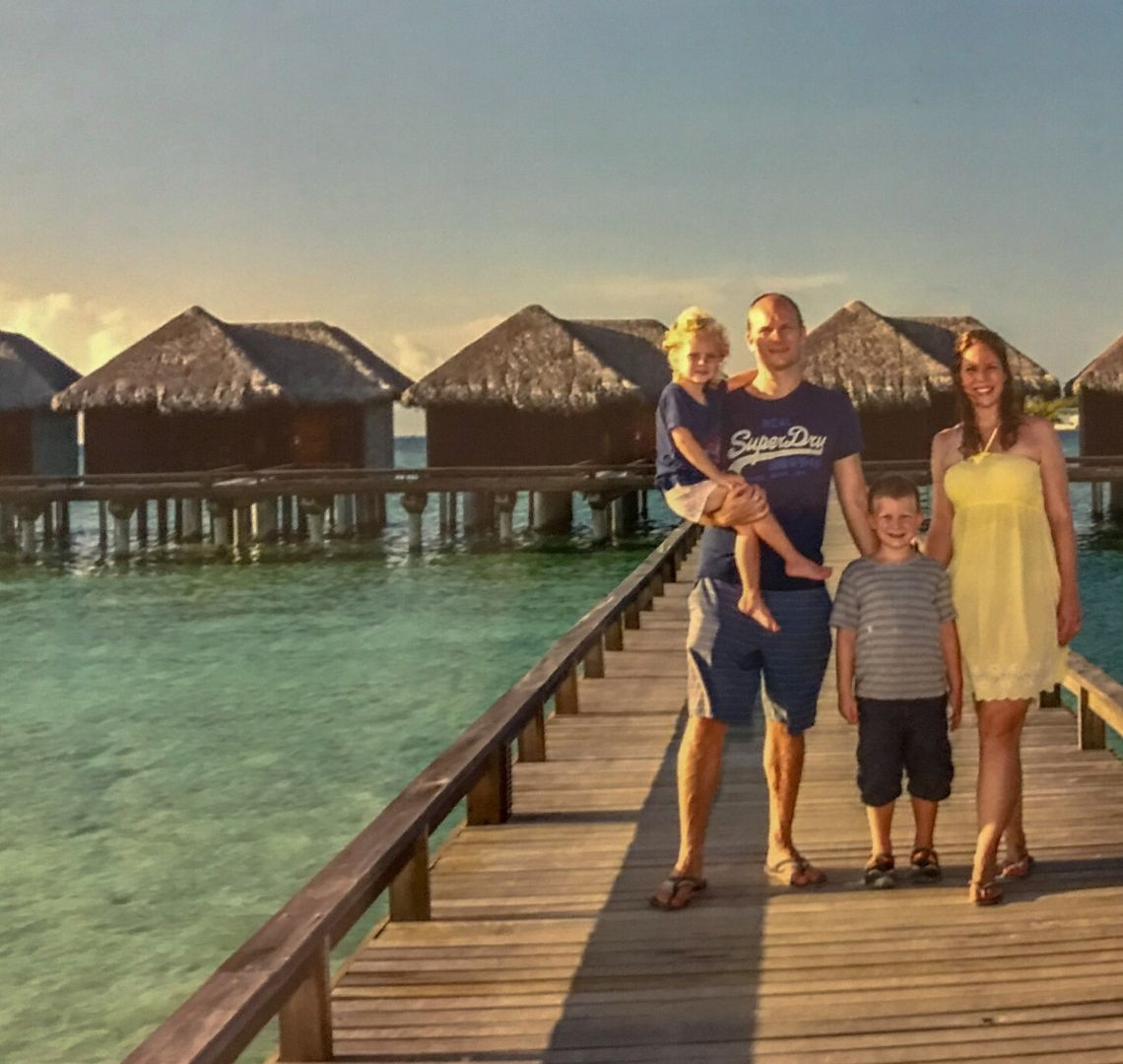 Maldives Activities / Things to do in the Maldives - family photo shoot. We are standing on a wooden deck with water bungalows behind us. Th
