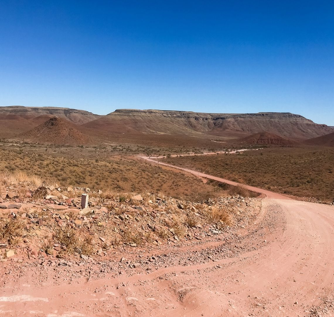 Driving for 2 weeks in Namibia is relentless, this image is of one of the many gravel roads twisting through a valley. The landscape is reddish brown with a few shrubs growing.
