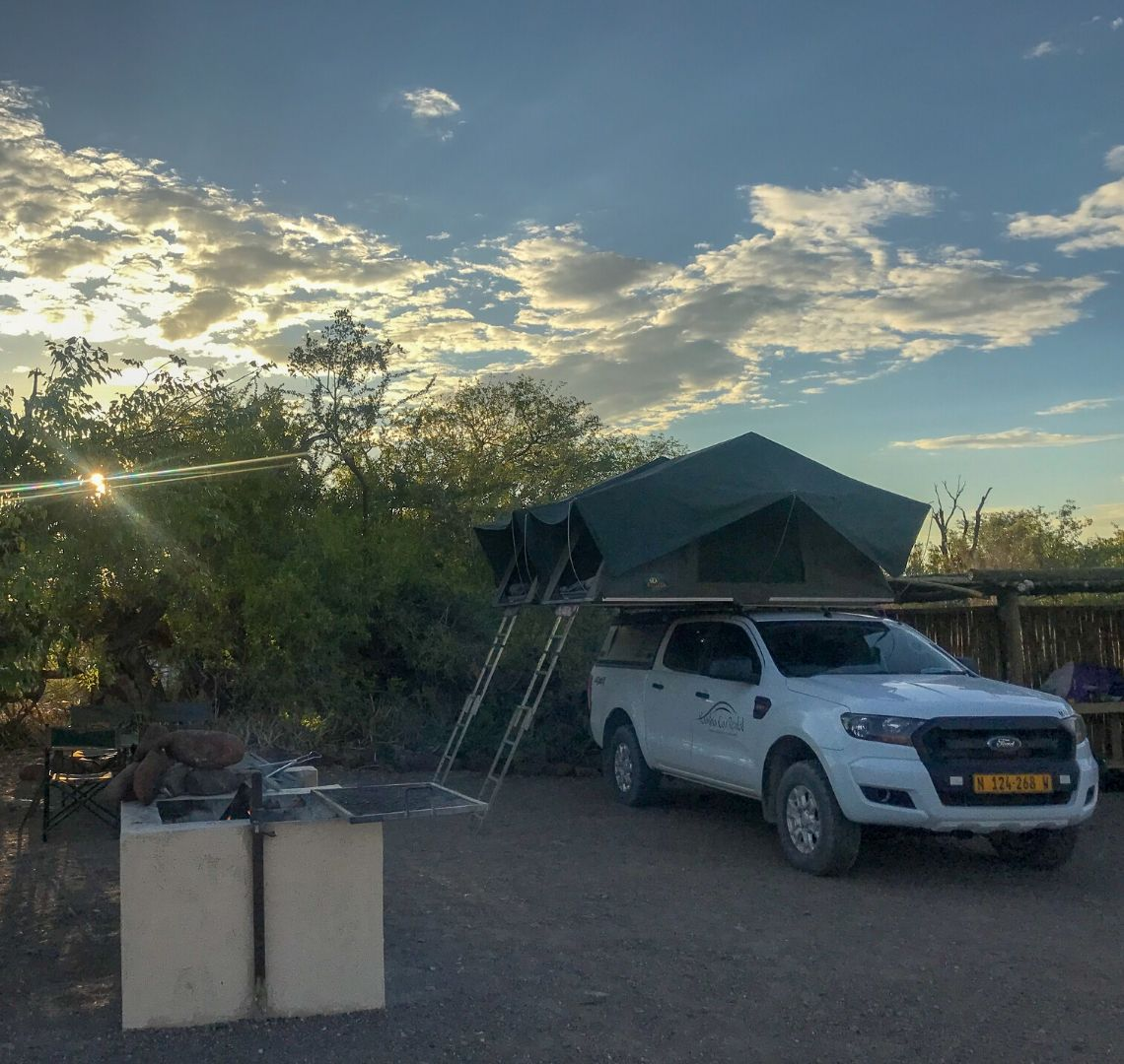 2 Week Namibia Itinerary - our campsite in Palmwag, there is the BBQ area in the left foreground. Behind it we had set up our tables. In the middle and to the right is the car with the tents already set up. Behind the car is a small wooden shelter where the sink and power points were.