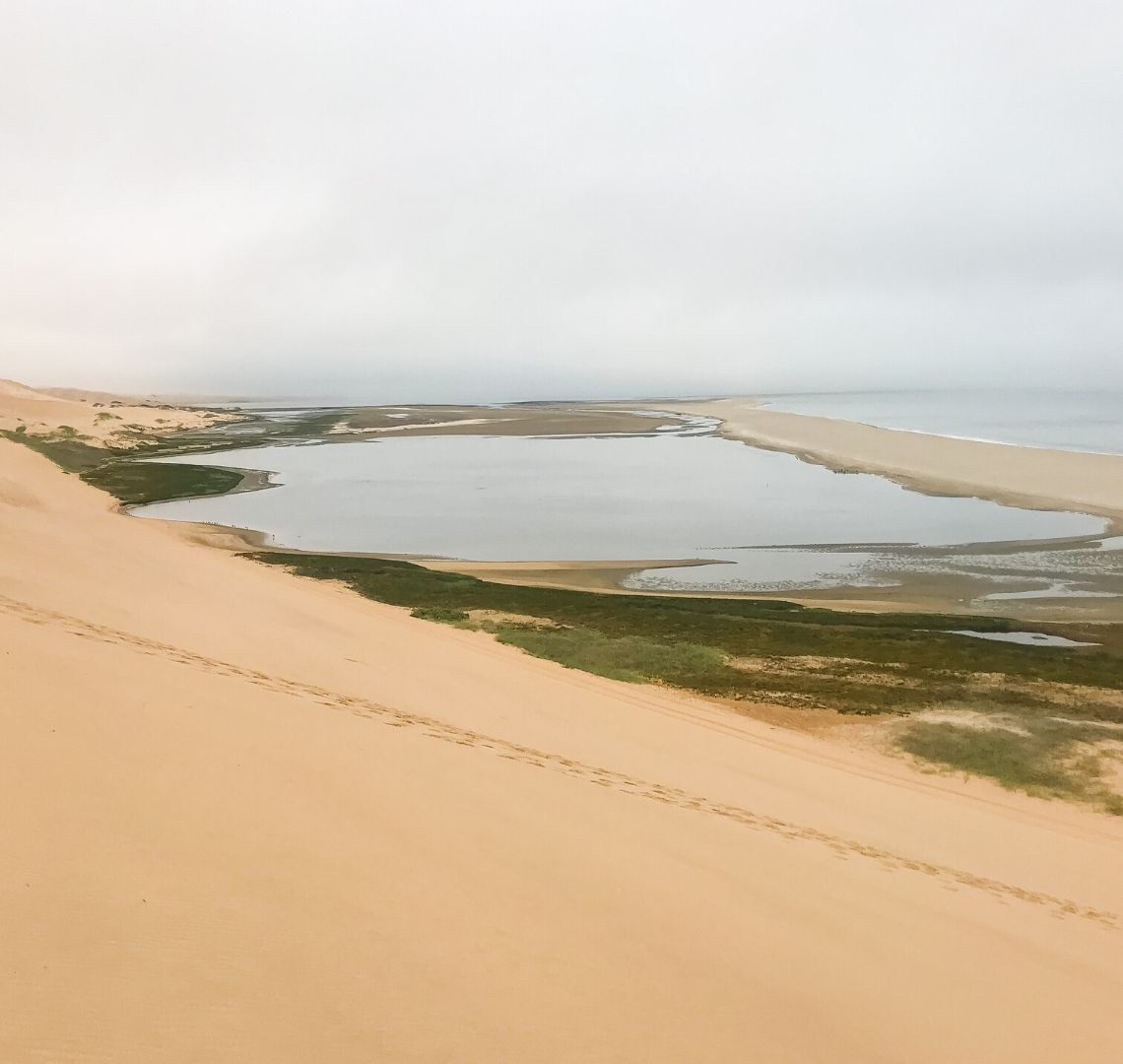 2 Week Namibia Itinerary - The sand dunes of Walvis Bay drop straight into the ocean in a very dramatic way. We climbed to the top and could see the sea lakes below us, then a sandbank and then the sea.