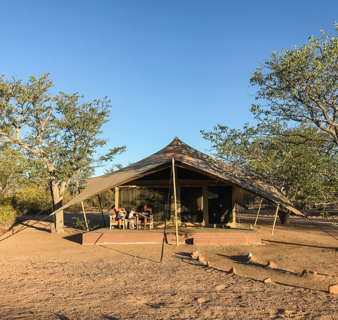 2 Week Namibia Itinerary - Mr Wanderlust and the Things sat outside a large clamping tent at Malansrus as the evening sun makes the colours softer and the shadows longer
