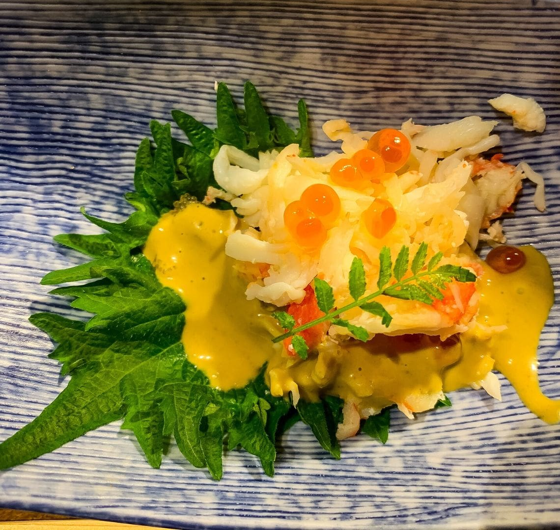 5 reasons to go family skiing in Niseko Wanderlust Family - a delicious starter of tiger prawn with cod roe on a yuzu leaf with yellow sauce all on a blue and white Japanese style plate