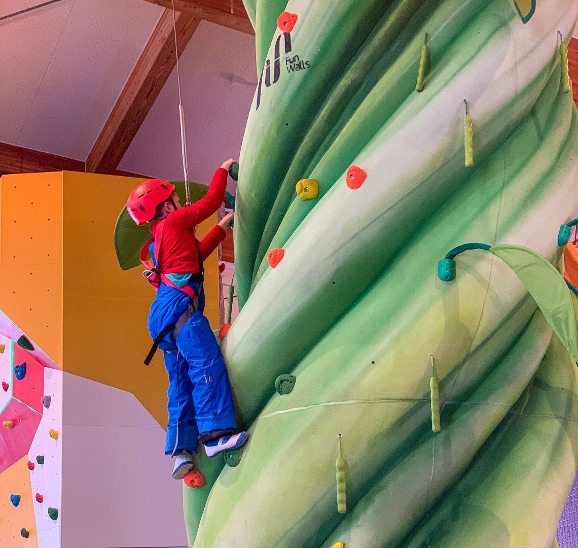 5 reasons to go family skiing in Niseko Thing 1 is wearing a bright red helmet, a bright red fleece and bright blue salopettes. He is near the top of a green climbing wall.