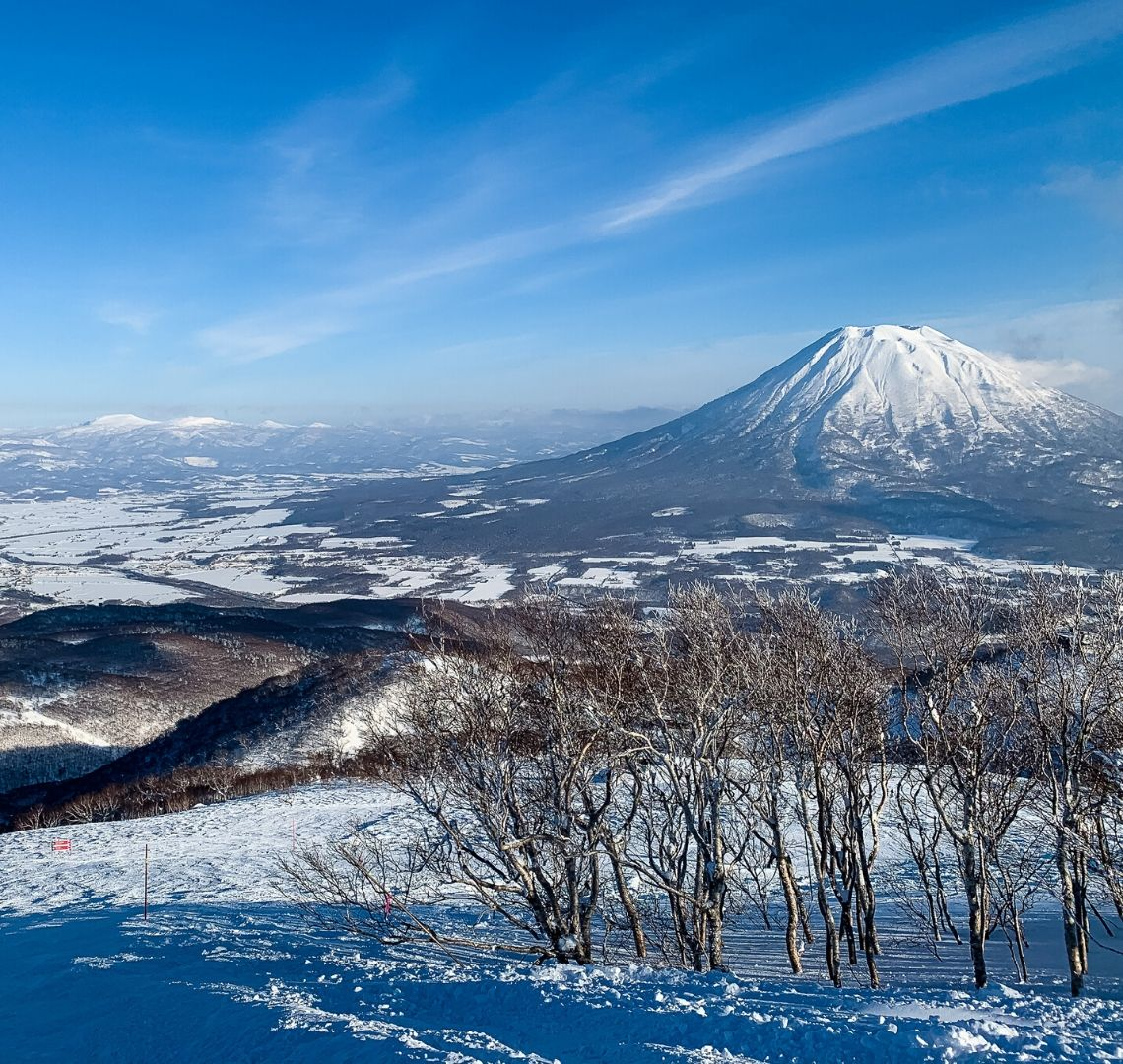 5 reasons to go family skiing in Niseko - Mount Fuji in the mid ground with other smaller mountains in the distance and trees in the foreground