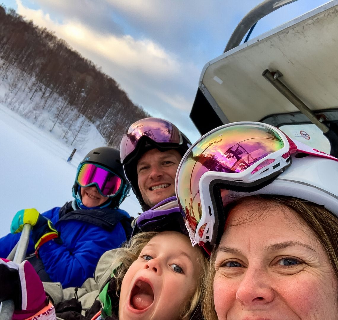 5 reasons to go family skiing in Niseko Wanderlust Family selfie on a ski lift - in order: me with my pink goggles wonky on my helmet, Thing 2 with pulling a funny face, Mr Wanderlust also with his goggles on his helmet and Thing 1 with rainbow goggles on, a black helmet and a bright blue jacket