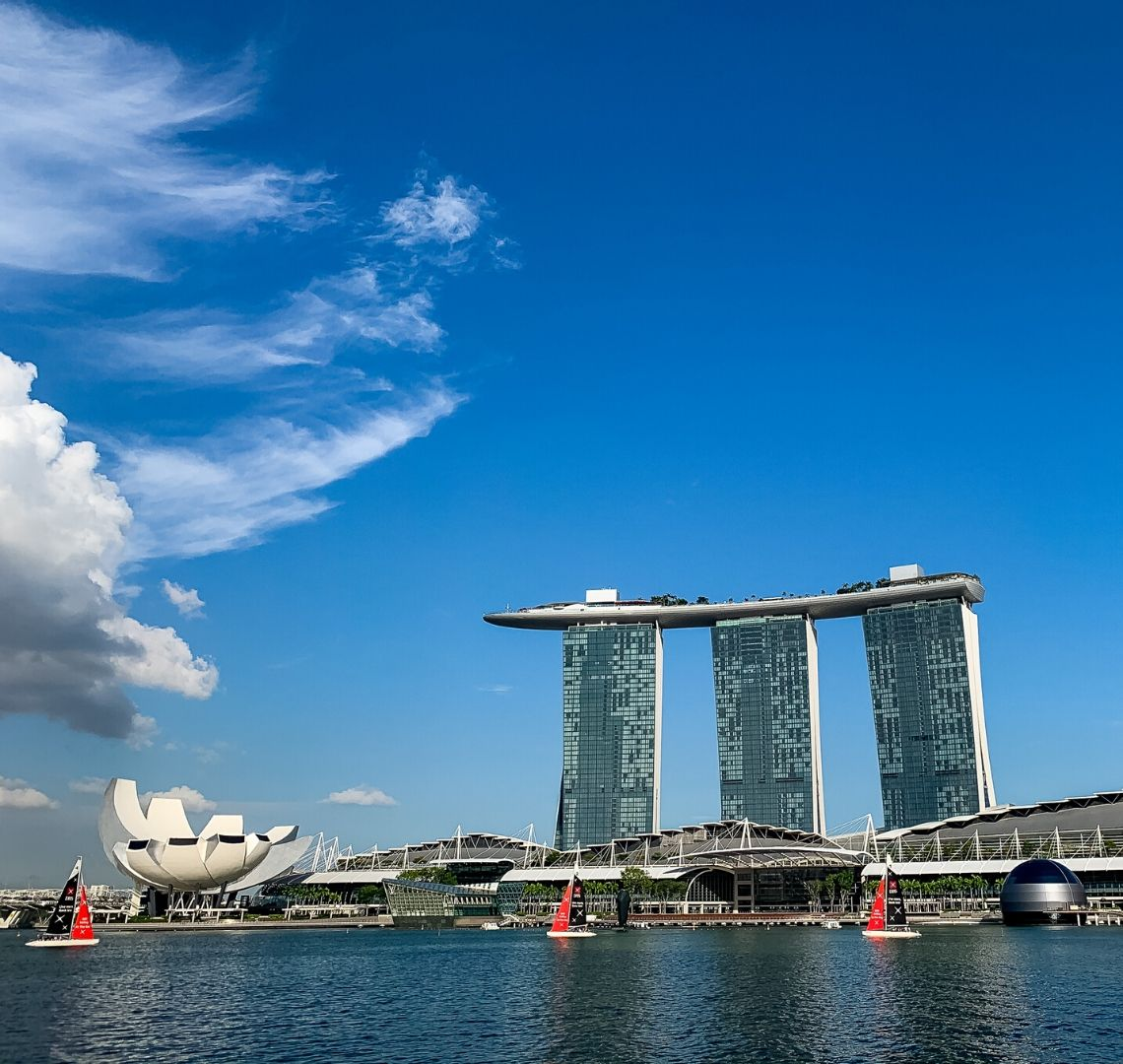 Things To Do In Singapore With Kids - view of Marina Bay Sands hotel from next to teh Merlion, there are sailing boats with red sails in the water between us and the hotel. The sky is bright blue and there are a few clouds to the left.