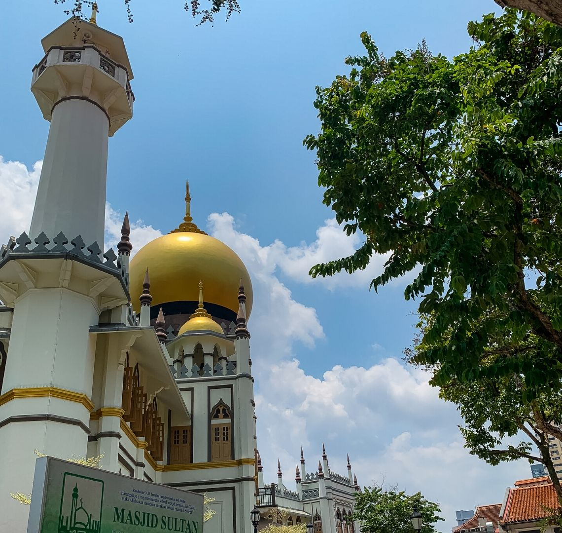 Things To Do In Singapore With Kids - the Sultan Mosque in Arab Quarter near Haji Lane has gold domes on the top and white walls. The decorations around the minarets are gold and grey. There is a tree to the right of the image.