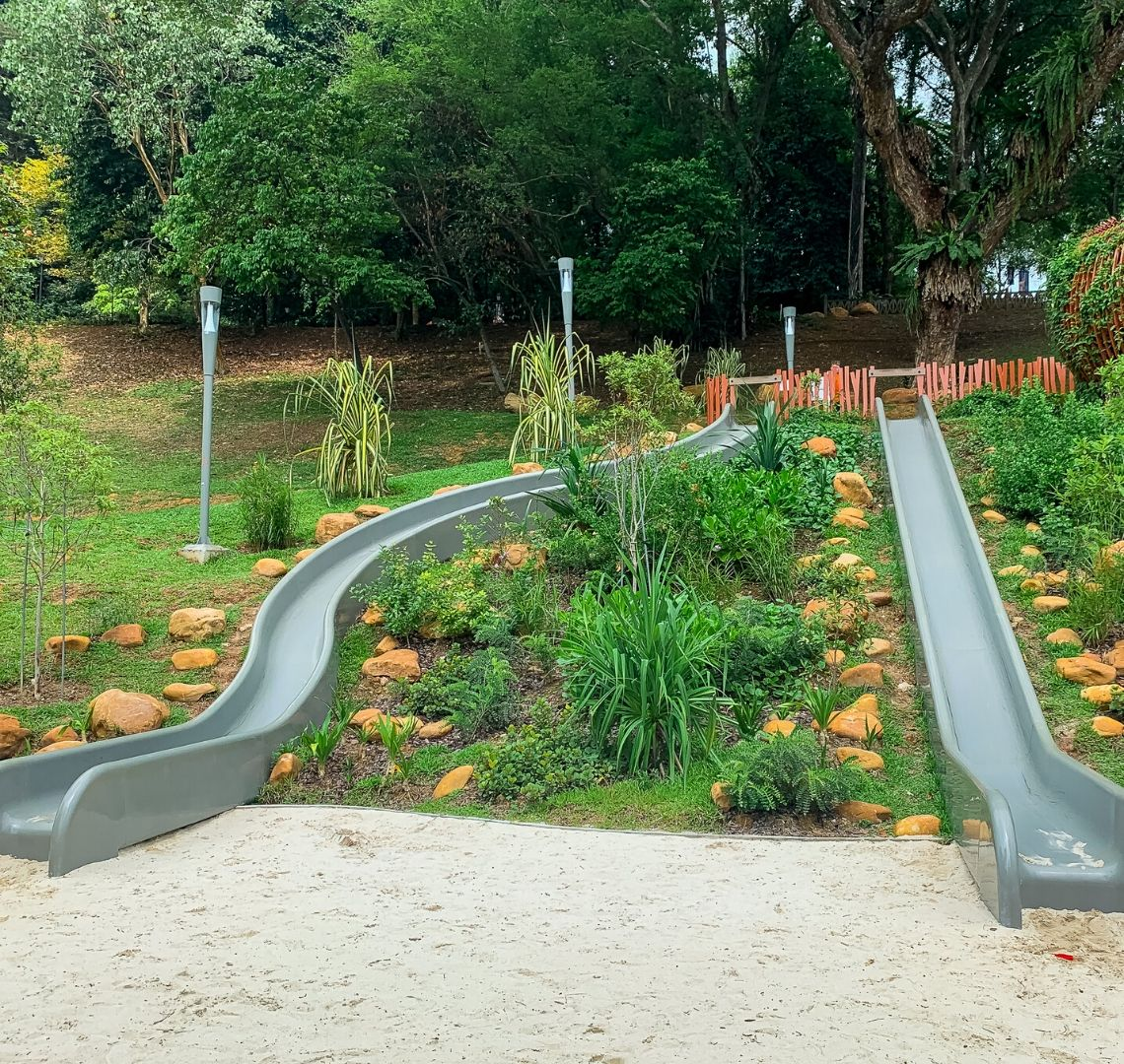 Playgrounds In Singapore With Kids - white industrial sand is at the bottom of 2 grey slides - one is completely straight while the other has some curves. Around them and in between them are grass, small shrubs and orangey stones. There are modern looking lampposts to the left curved slide and a faux fence at the top. Behind that there are trees.