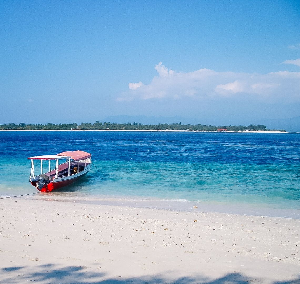 Best Secret Islands in Indonesia - white white sand leads to turquoise water which then turns a deeper but bright blue. In the distance is another island with a thin white strip of sand and some trees and a building. In the shallows on this side, just pulled up to the beach is a red bottomed boat with white sides and a faded red roof.