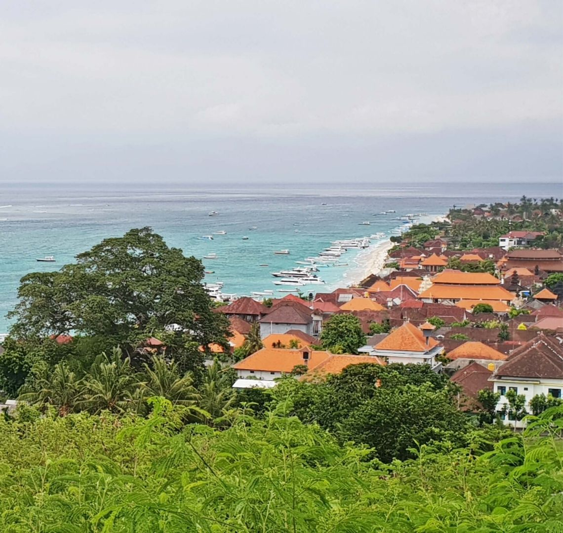 Best Secret Islands in Indonesia - the photo is taken from a hill. There are some ferns in the foreground and then lots of red and orange grooves of houses with white walls. Beyond that you can see the beach where there are lots of boats moored in the shallow turquoise water. As the water gets deeper it turns darker.