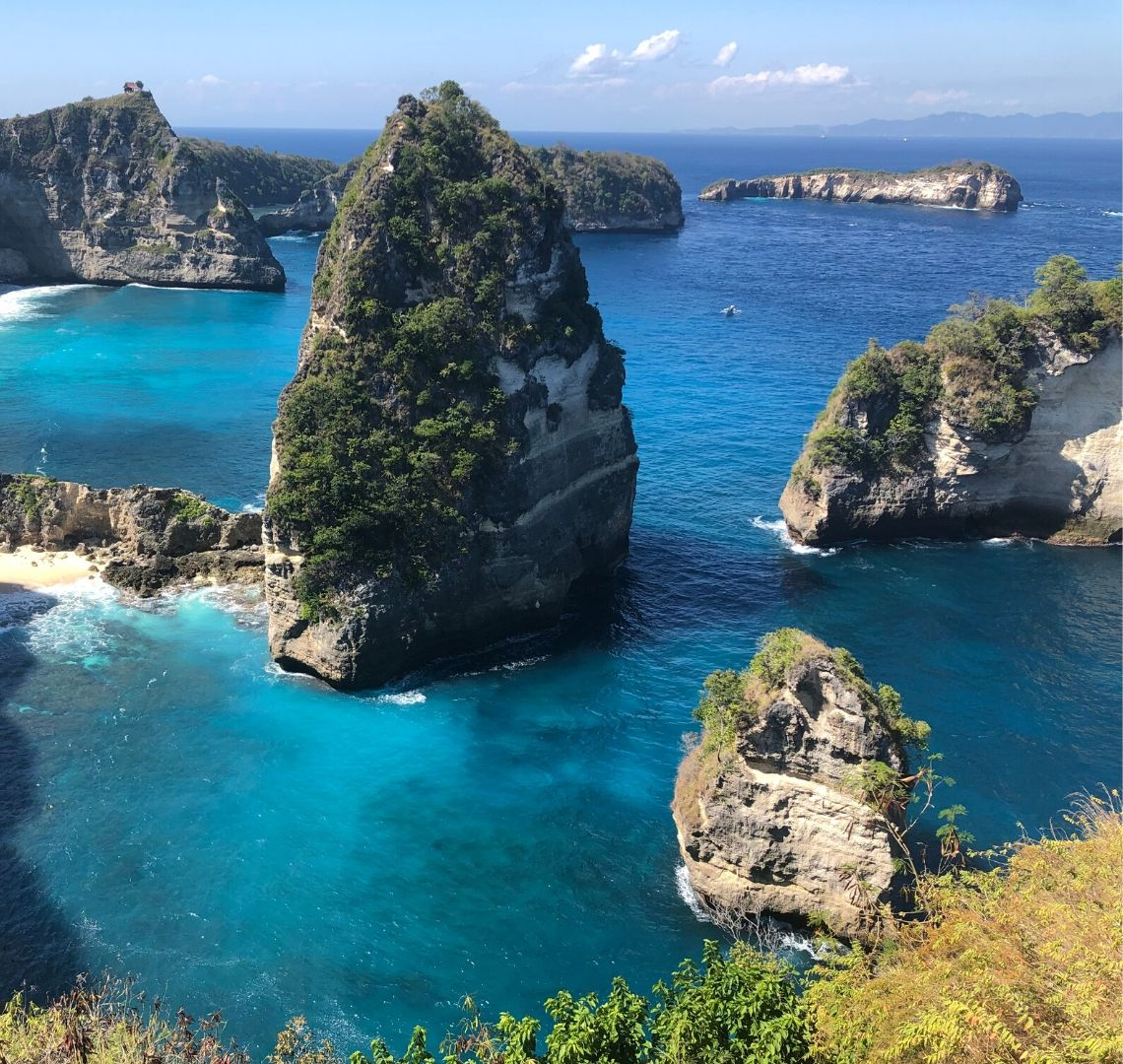 Best Secret Islands in Indonesia - the photo is taken from the top of a cliff. At the bottom you can see the grasses and then nothing as the cliff face drops away. The sea below is bright blue and there are really tall rocky islands of varying sizes with trees on top and growing out the sides. In the distance is a tiny boat.