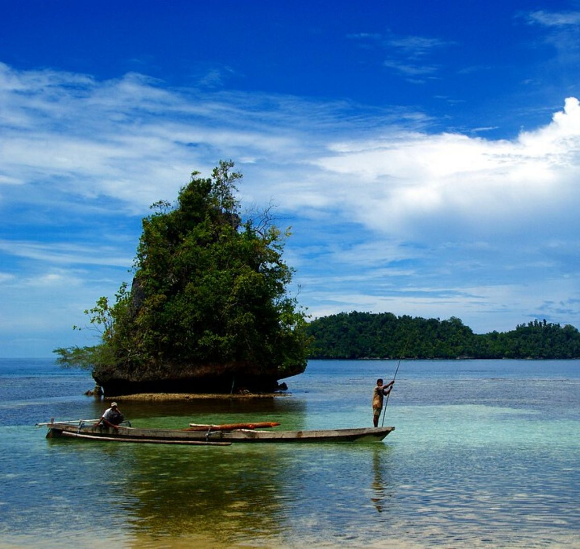 Best Secret Islands in Indonesia - two men sail past on a long boat. The one at the very back is steering and the one at the front is holding a long pole. They are in crystal clear shallow water and you can see the rocks and seaweed at the bottom. Behind them is a tiny island which basically looks like a tree. Behind that after an expanse of water are more trees