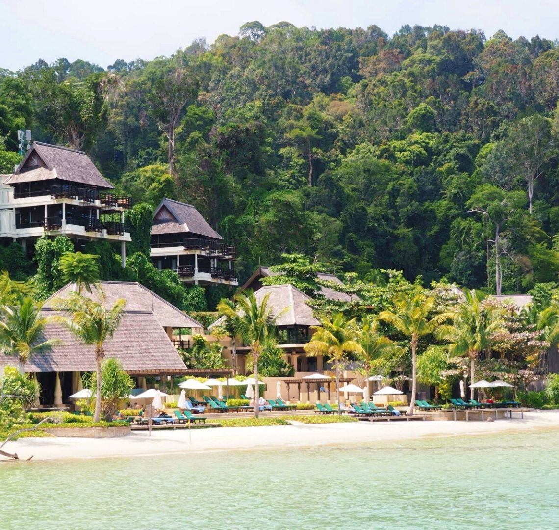 Best Secret Islands In Malaysia - Gaya Island Resort as viewed from the sea. The sea is a soft turquoise, then there is the beach with bright turquoise sun loungers neatly arranged under parasols. The main hotel buildings are behind and then, built into the hill you can you see some of the hotel rooms