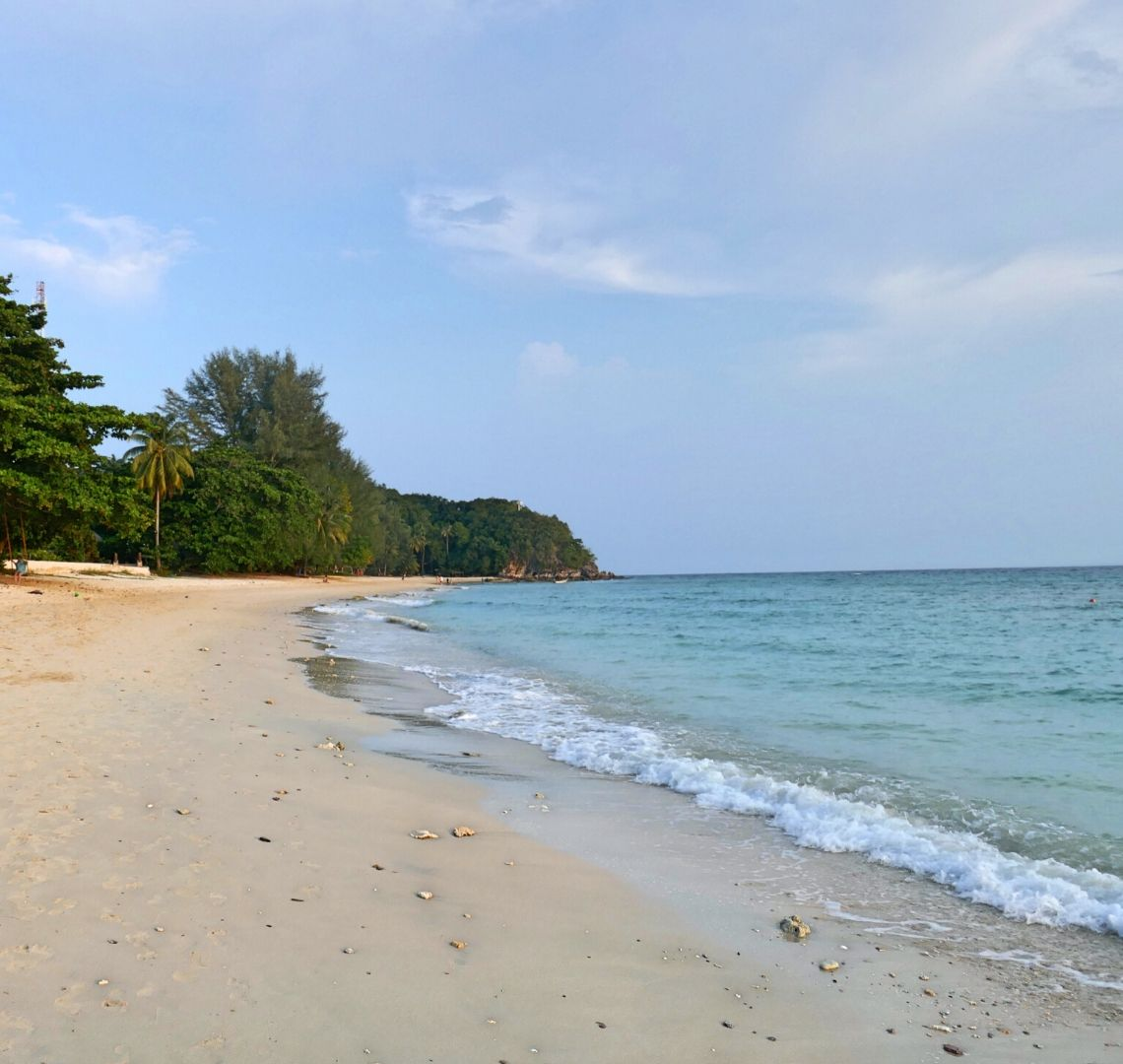 Best Secret Islands In Malaysia - Kapas - there are a few rocks strewn along a sandy beach. There are some trees and a palm tree further down the beach. A small wave is breaking on the beach in the middle of the image and to the right is the sea which is turquoise.