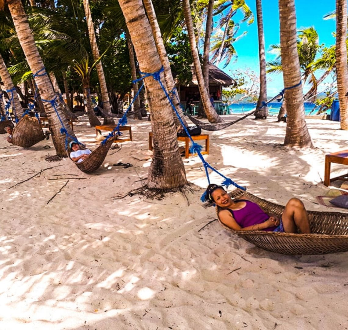 Inaladelan - there are three hammocks strung up between palm trees and two behind them. A lady in the first hammock is smiling at the camera. She is wearing a bright purple top. There is a hut with a thatched toof behind all the trees and the turquoise and blue sea can be glimpsed in teh background.