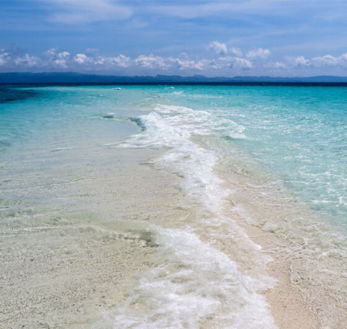 Best Secret Islands in the Philippines - there is perfectly clear, turquoise water on either side of a white sandbar. There are frothy waves in teh middle. To the very edges of the image and in the distance, the sea turns a rich deep blue.