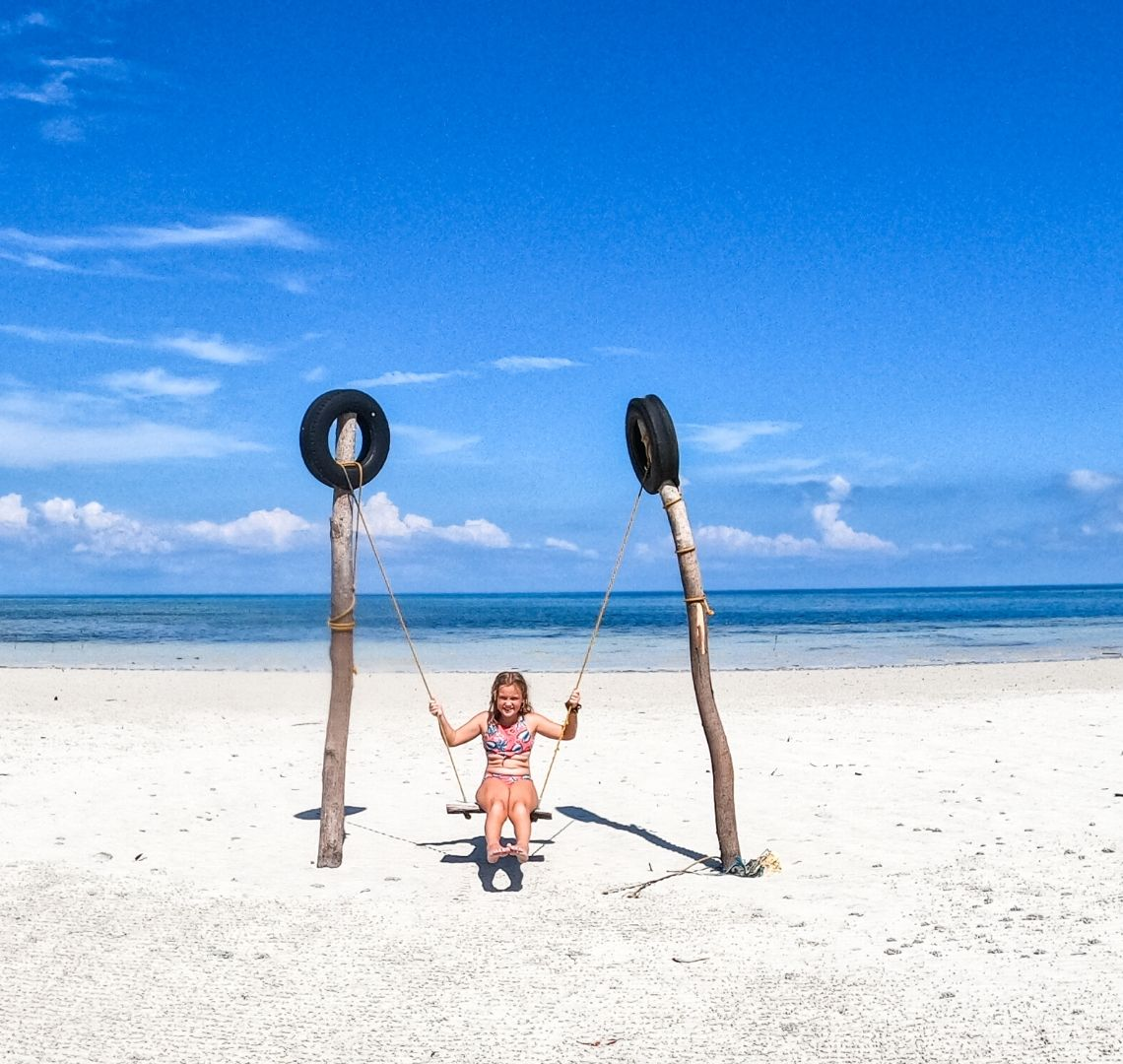 Siquijor - There is a vast expanse of white sand and beyond is deep blue sea and bright blue sky with just a few wispy clouds up high and some fluffier ones on the horizon, A little girl sits on.a swing in the centre of the photo - it is strung up between two large wooden poles with black tyres fixed to the top