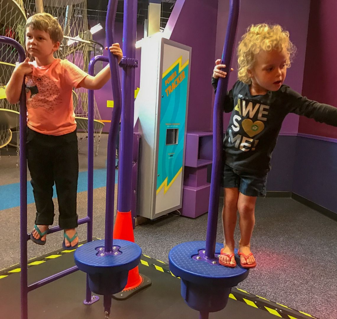 Thing 1 on the left in an orange t-shirt, black trousers and flip flops. Things 2 is in a black top with AWESOME written on it, denim shorts and flip flops. They are climbing and balancing on a purple exhibit at the Children's Museum of Houston