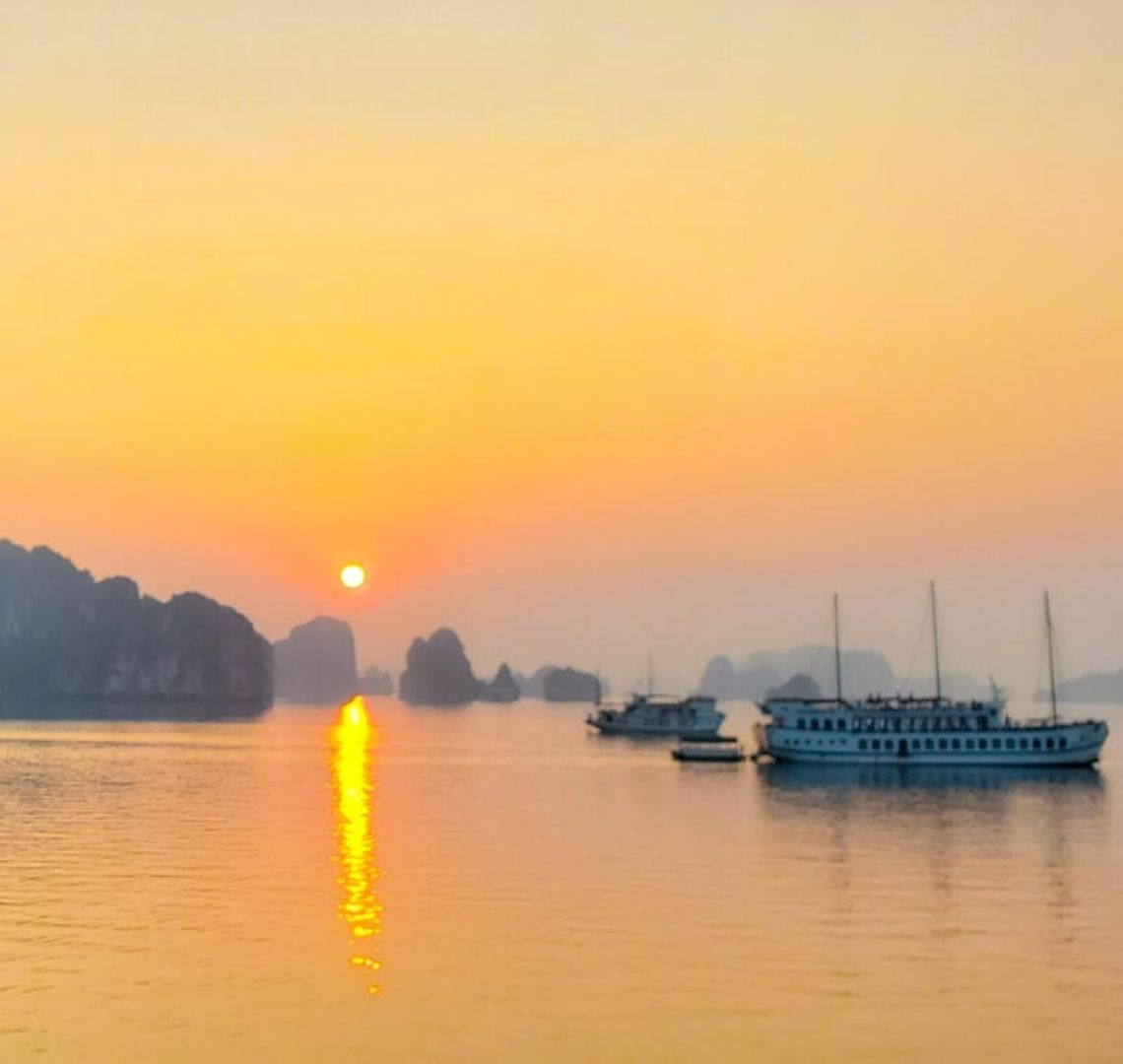 The sun is setting in Bai Tu Long in Halong Bay. There are junk ships on the still water in the foreground and shadowy limestone rocks and islands in the background. The sky is bright orange and the tiny setting sun sets off an orange stripe in its reflection in the water.