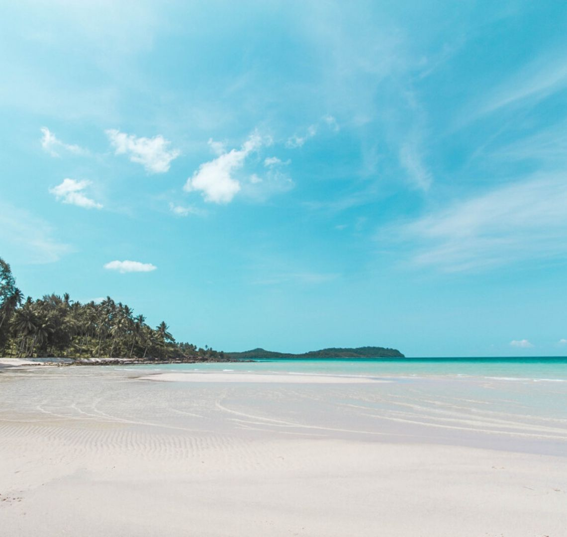 Koh Kood beach has white white sand and bright turquoise water. On the left are a collection of palm trees and above is a bright blue sky.