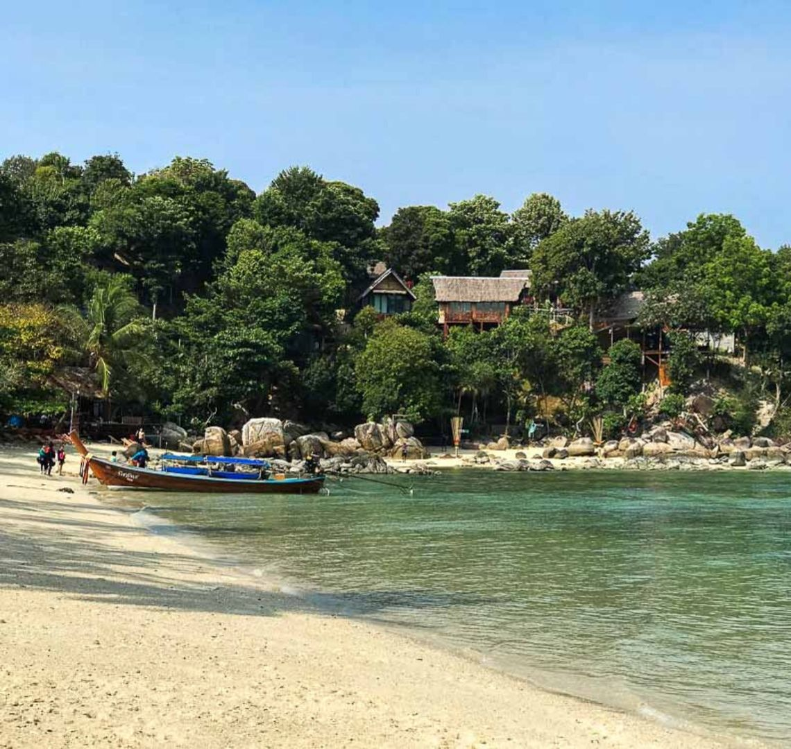 Best secret islands in Thailand with kids - the beach in Koh Lipe bends around to the left. There is a boat moored on the beach with some people on it and next to it. Behind it are a few rocks and trees. There is a hotel or guest house nestled in the trees slightly above the beach