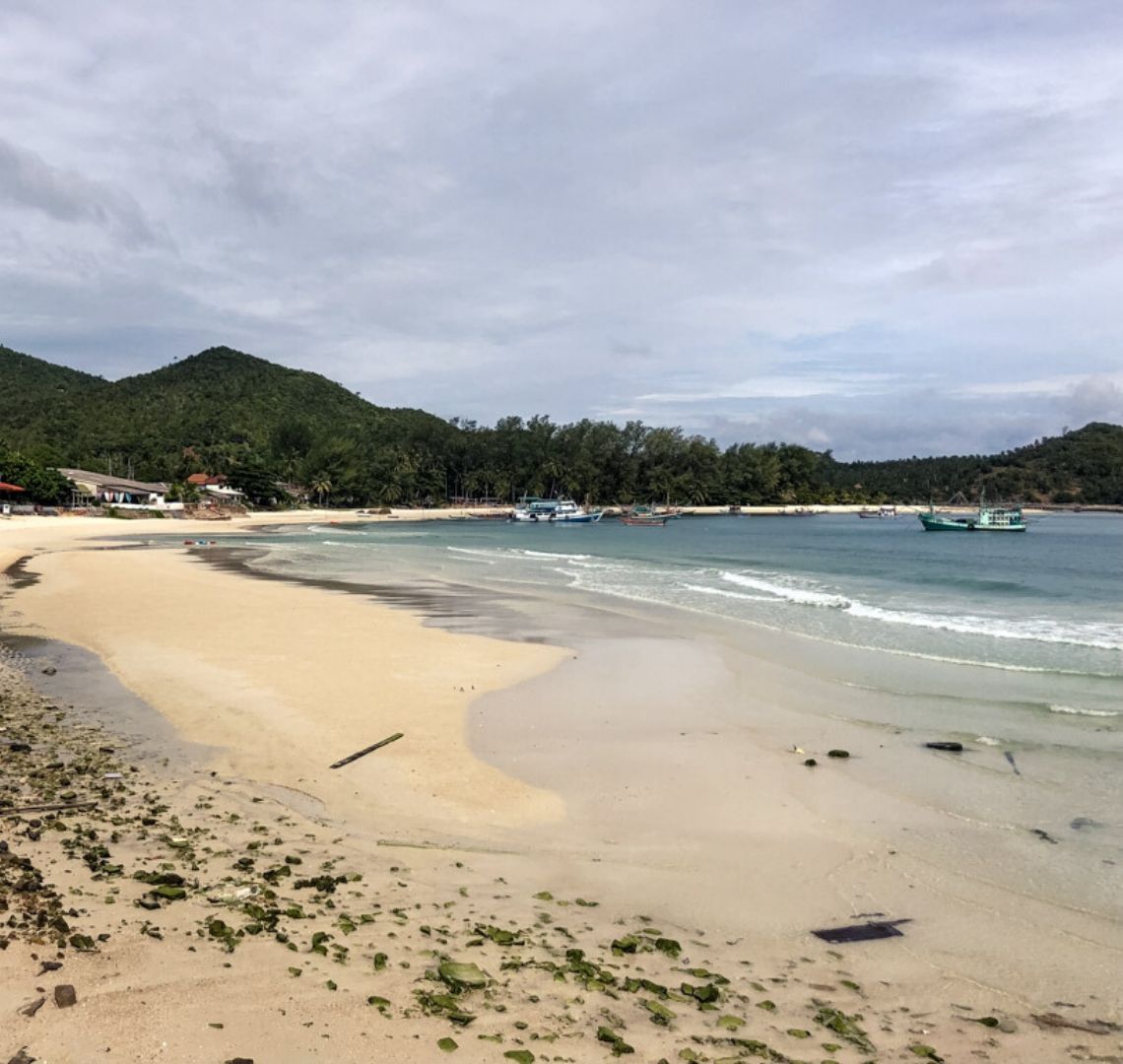 The white sand of Koh Phangan stretches in front and then bends around to the right, In the blue sea there are a few colourful boats. Just off the beach are a few buildings. Behind them are some tree covered hills. The sky is cloudy.