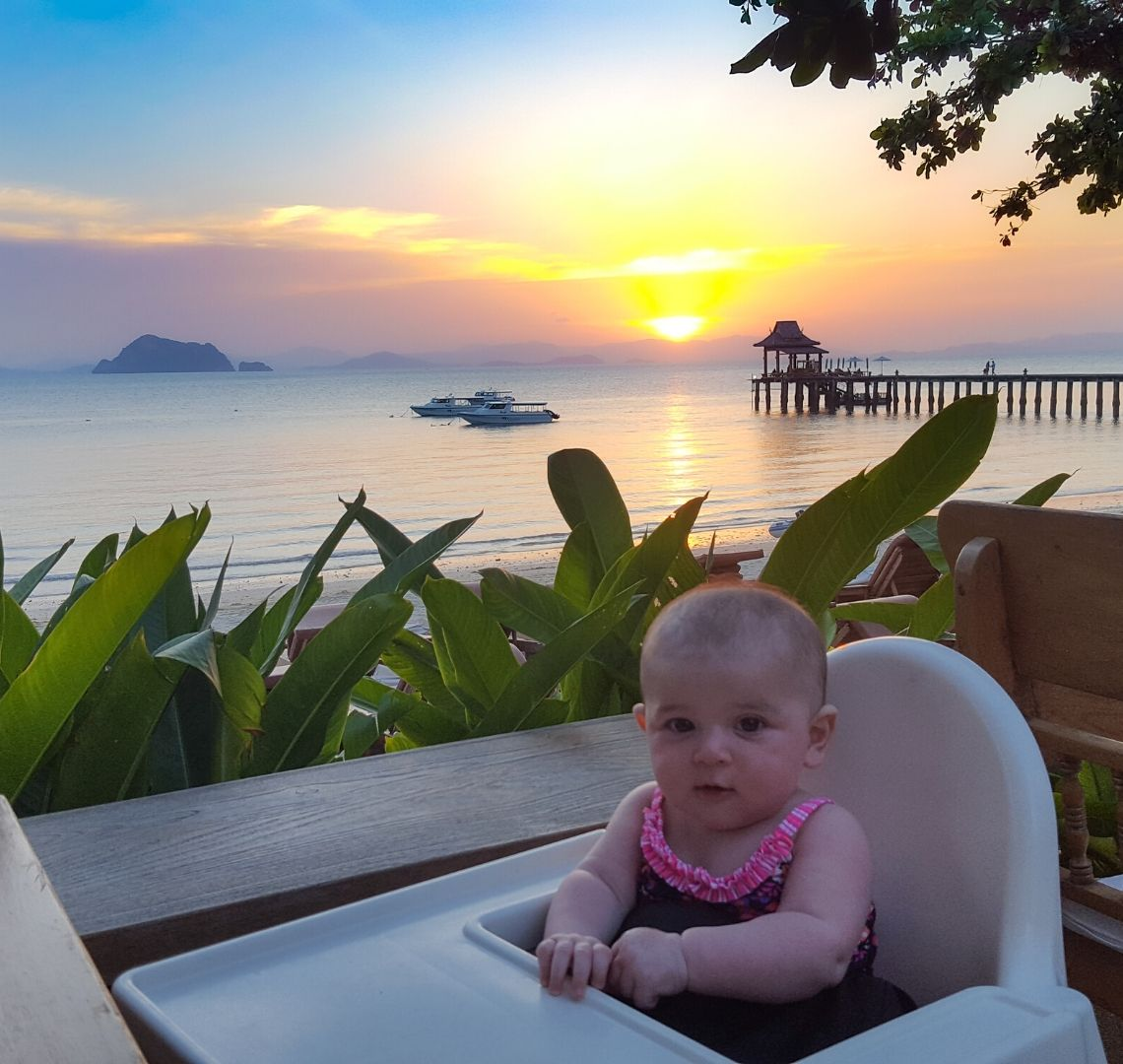 A baby in a white plastic high chair is in the foreground. Behind her there are some ferns and then the beach. There are 2 boats and a pier going into the calm sea waters and some islands in the distance. There is a rainbow of colours in the hazy sky and a bright yellow sun is setting on the horizon.