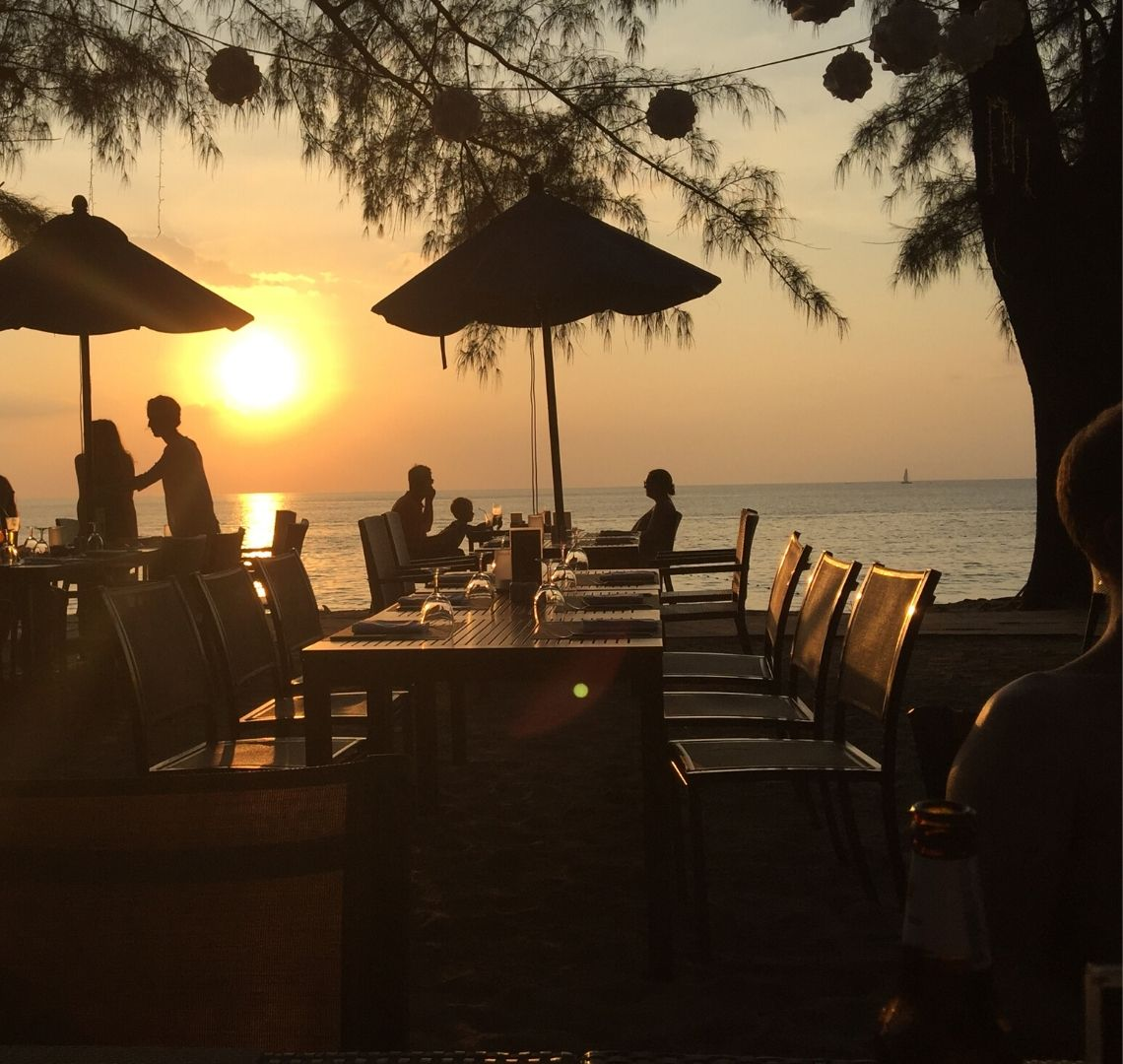 Best secret islands in Thailand with kids - the sun is setting over the sea at the beach in Phuket, in teh foreground are shadowed tables with umbrellas with a few people dining, a tree and some hanging lights that aren't yet on.