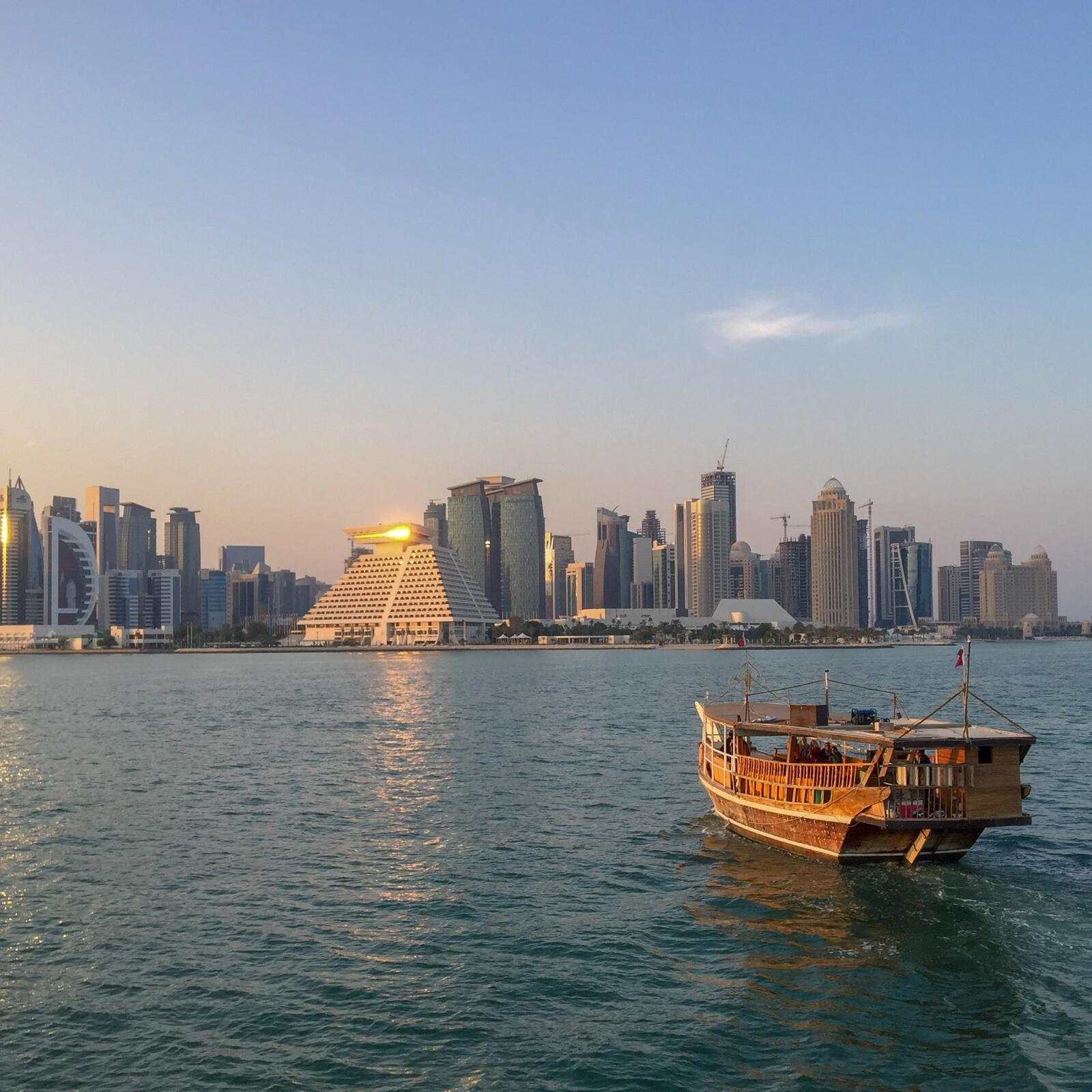 Qatar One Year On - Doha skyline at dust with a dhow boat in the aqua waters on the right