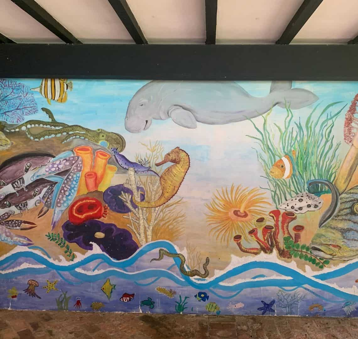 A mural of a sea scene with marine life such as a dugong, a sea horse, a clown fish, an anemone and a crab.