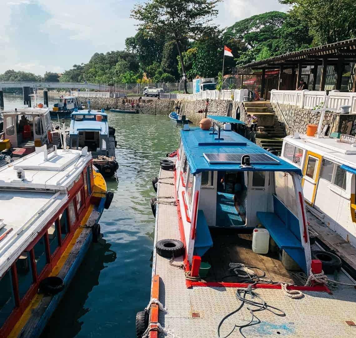 Several bumboats on the water at the jetty at Changi Point Ferry Terminal. They are brightly painted in blues, reds and yellows.